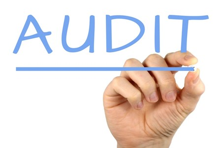 A picture showing a person writing the word Audit
