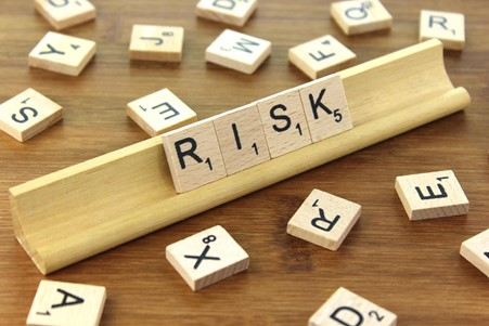 A picture showing the word risk made out of scrabble tiles